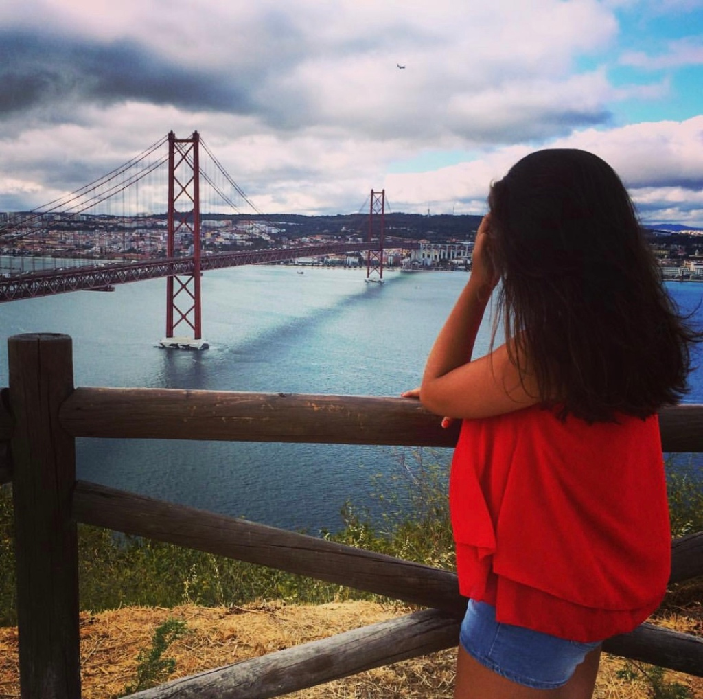 25th of April Bridge over the Tagus river in Lisbon, Portugal. Girl in a red top